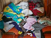 A Lot Of Different Clothes On The Couch. A Mess Of Clothes. Ironed Clothes poster