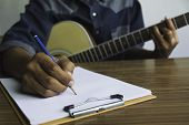 Composer Holding Pencil And Writing Lyrics In Paper. Musician Playing Acoustic Guitar. poster