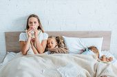 Sick Woman Sneezing In Napkin While Sitting In Bed Near Diseased Children poster