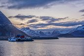 Beautiful View Of A Red Fishing House And A Boat, With The Snow Covered Mountains In The Background, poster