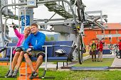 Happy couple traveling by chair lift enjoying landscape