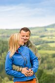 Lovely young couple cuddling with scenic landscape