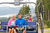 Chair lift going through forest while happy couple sitting