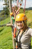 Smiling woman climbing on high wire in adventure park