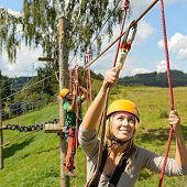 Young woman climbing in adventure park with friend summer free time