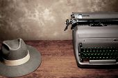 An old vintage typewriter with a reporter's fedora hat on a wooden table with room for copy.