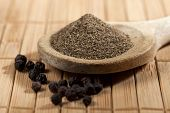 picture of peppercorns  - heap of powdered black pepper on a wooden spoon and pepper corns - JPG