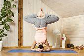 An image of a pretty woman doing yoga at home - Baddha Konasana Shirshasana