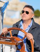 Mature Man Holding Steering Wheel Of Sailboat, Outdoors