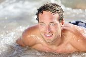 Beach man having fun in water smiling happy. Portrait of young handsome male beach model surfing on
