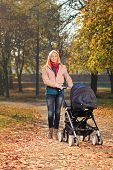 A smiling mother with a baby carriage having a walk in a park in autumn
