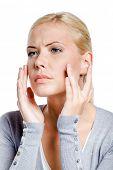 Mujer examinando su cara y las arrugas que pueden aparecer, aislado en blanco