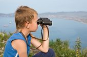 Boy looking through binoculars from the top of the mountain. In the background of the sea coast.