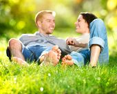Happy Smiling Couple Relaxing on Green Grass. Spring Park. Young Couple Lying on Grass Outdoor. Barefoot