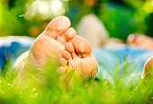 Young Couple Lying on Green Grass outdoor. Spring. Bare feet. Barefoot. Healthy Foot