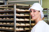 Female baker baking fresh bread rolls in the bakehouse