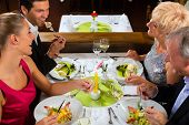 Family, mother and father with adult children and daughter or son in law �?�¢??fine dining in nice restaurant or hotel