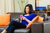 Indonesia joven sentado en el sofá con el texto con un teléfono móvil o Smartphone