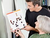 Senior woman with male hair stylist selecting hair color from catalog at salon