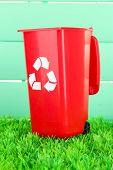 Recycling bin on grass on light blue background