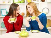 Duas amigas conversar e beber chá na cozinha