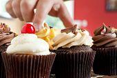 Mão agarrando um Cupcake de Gourmet