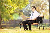 Young smiling businessperson sitting on a wooden bench and working on a laptop in a park