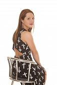 stock photo of cross-dress  - A woman is sitting in a chair wearing a dress with crosses on it - JPG