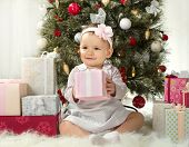 foto of solemn  - one-year-old little girl solemnize Christmas sit under Christmas-tree with gift