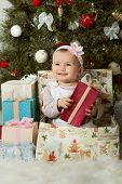 stock photo of solemn  - one-year-old little girl solemnize Christmas sit under Christmas-tree with gift vertical photo