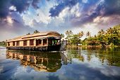 stock photo of indian blue  - House boat in backwaters near palms at cloudy blue sky in Alappuzha Kerala India - JPG