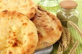 Pita breads on wooden stand with spices and spikes on tablecloth close up