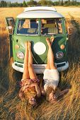 stock photo of caravan  - Attractive  women lying in the grass in front of an old caravan bus - JPG