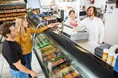 image of deli  - Couple purchasing meat from salesman at counter in butcher - JPG