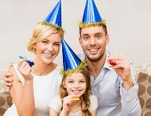 celebration, family, holidays and birthday concept - three smiling women wearing blue hats and blowi
