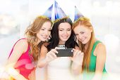 celebration, friends, bachelorette party, birthday concept - three smiling women in blue hats having fun with smartphone photo camera