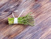 Bunches Of Asparagus Tied On A Wood Background.