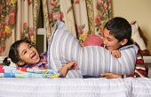 stock photo of pillow-fight  - Siblings Enjoying a Pillow Fight at Home - JPG