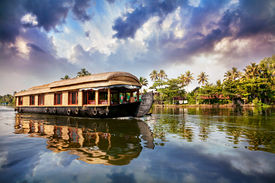 stock photo of alleppey  - House boat in backwaters near palms at cloudy blue sky in Alappuzha Kerala India - JPG