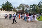 KANDY, SRI LANKA - FEBRUARY 26, 2014: Tourists in front of The Temple of the Tooth Relic, one of the