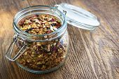 Homemade granola in open glass jar on rustic wooden background