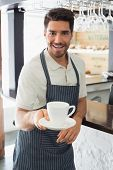 Young waiter smiling and holding cup of coffee at the caf�?�©