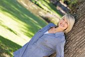 Tilted image of happy woman leaning on tree trunk in parkland