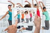 Hand holding tablet pc against dance class in gym