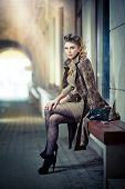 Attractive blonde girl wearing short dress and high heels - urban scene. Fashion model
