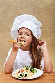 Happy smiling chef child eating a creative spaghetti dish