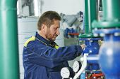 stock photo of hvac  - repairman engineer of fire engineering system or heating system open the valve equipment in a boiler house - JPG
