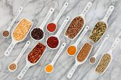 Herb and spice selection in metric measuring spoons and scoops  over marble background.