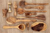 Olive wood kitchen utensil selection over papyrus background.