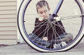 Sad boy looking at his flat bike tire